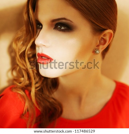 Beautiful ginger girl in orange dress with smoky eyes and diamond earring. Close up. Studio shot