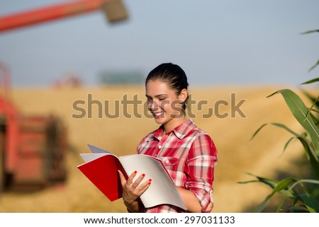 Beautiful girl agronomist with note book standing in golden wheat field, combine harvesting in background