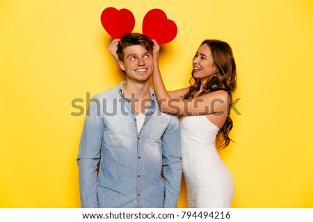 Beautiful girl and attractive celebrating St. Valentine's day, have fun together, joking, playing with hearts attributes. Dressed in jeans shirt and white dress. #794494216