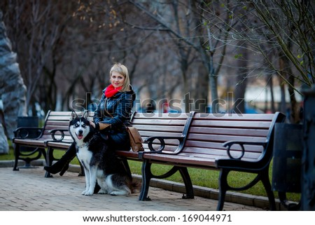 beautiful girl and dog Huskies walking around the city, the owner of the dog sitting on the bench