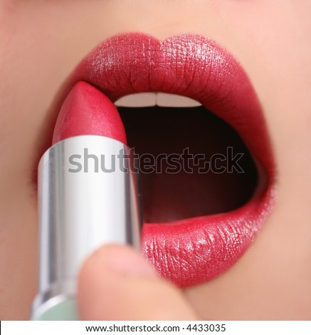 Beautiful girl applying red lipstick, silver holder
