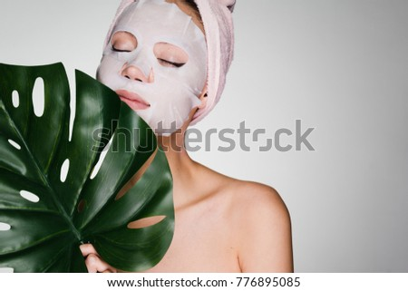 beautiful girl arranged a day spa, on the face a tissue mask, holds a green leaf