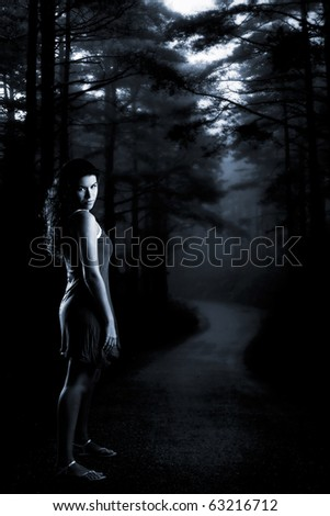 Beautiful girl at night in the middle of a dark forest