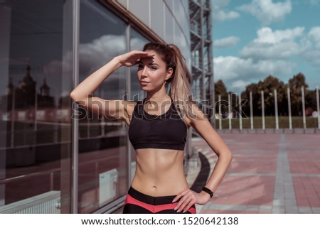 Beautiful girl athlete, covers distance into distance with hand from sun, glass windows background, summer spring city, free space motivation, sportswear, active fitness lifestyle, outdoor sports . #1520642138