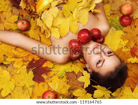 Beautiful girl Autumn lying over yellow leaves carpet