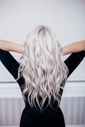 beautiful girl back with silver grey ash blonde curly wavy long hair in black dress isolated