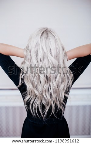 beautiful girl back with silver grey ash blonde curly wavy long hair in black dress isolated ストックフォト ©