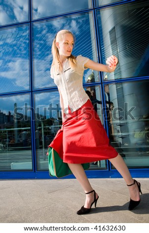 Beautiful girl, blond, runs against the backdrop of the station. In all growth.