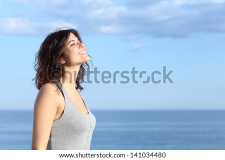 Beautiful girl breathing and smiling on the beach with the sea and blue sky in the background - Shutterstock ID 141034480