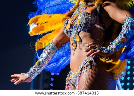 Beautiful girl bright colorful carnival costume dark background. Afro-Americans woman samba dancer carnival costume with feathers rhinestones black background