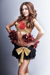 Beautiful girl cheerleader posing at studio.