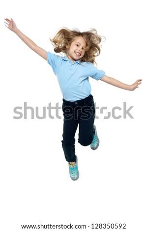 Beautiful girl child jumping high in air, arms outstretched sideways.
