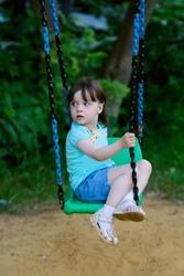beautiful girl child 3 years old with a bang in a blue t-shirt and shorts swinging on a swing in the yard.