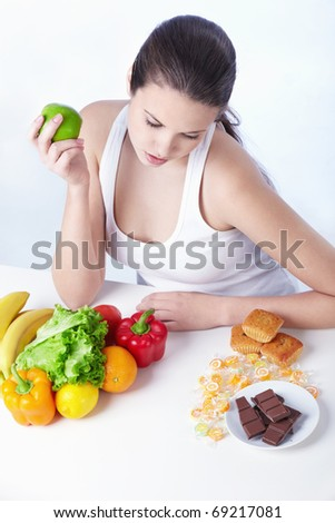 Beautiful girl choose between healthy food and sweet on a white background