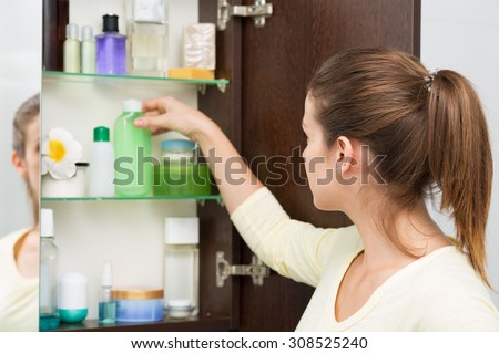Beautiful girl choosing beauty products from the bathroom cabinet
