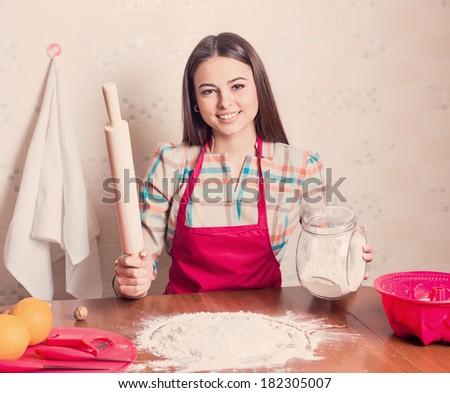 beautiful girl cooking cake in kitchen