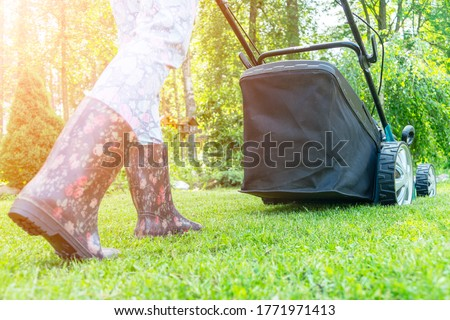 Beautiful girl cuts the lawn. Mowing lawns. Beautiful woman lawn mower on green grass. Mower grass equipment. Mowing gardener care work tool. Close up view. Lawn mowing
