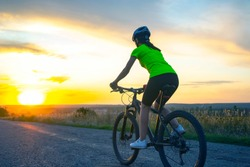 Beautiful girl cyclist rides a bicycle on the road in the sunset. Healthy lifestyle and sport. Leisure and hobbies