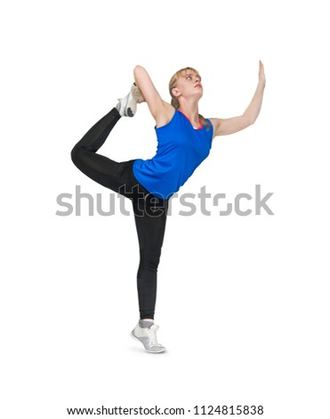 Stock Photo beautiful girl doing exercises on a white background. gymnast standing on one leg. Girl athlete blonde beauty keeps her leg during exercise for flexibility. blue t-shirt and black tight leggings.