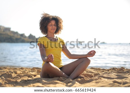 Beautiful girl doing yoga at the beach