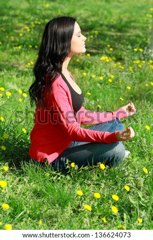 Beautiful Girl Doing Yoga Exercises in the park on green grass