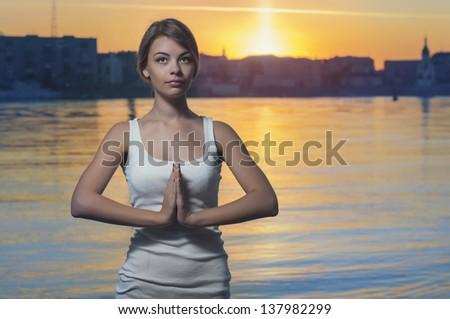 Beautiful girl doing yoga on the lake - stock photo