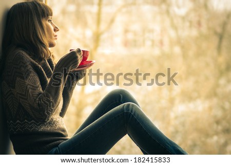 Beautiful girl dreaming with cup of coffee or tea near window