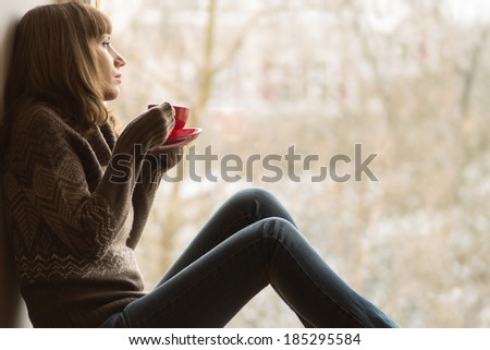 Beautiful girl dreaming with cup of coffee or tea near window