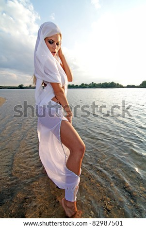 Beautiful girl dressed in arab costume dancing on the beach in the sunset