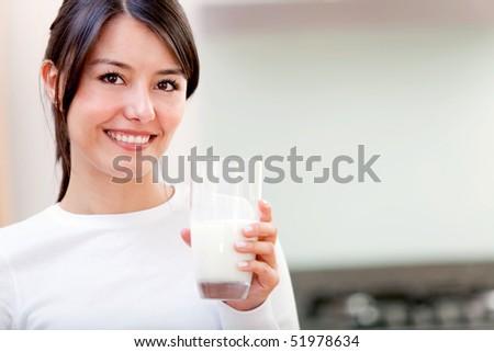 Beautiful girl drinking a glass of milk