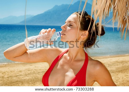 Beautiful girl drinking water against blue sea