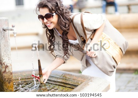 beautiful girl drinking water from a fountain