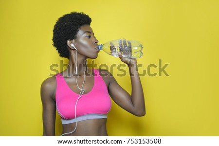 Beautiful girl drinking water while doing sport