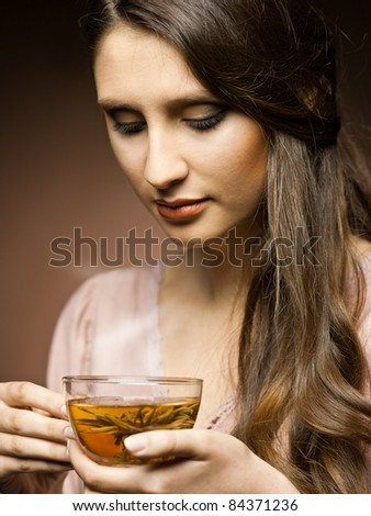 beautiful girl drinks tea  in the kitchen