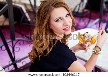 beautiful girl eating an ice cream with fresh fruits outside
