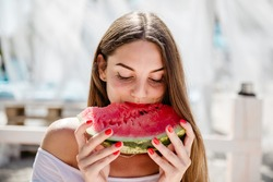 Beautiful girl eating watermelon in bungalow on the beach