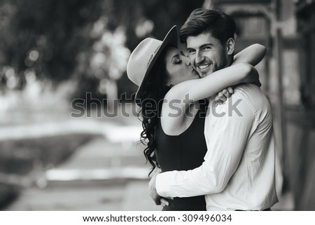 beautiful girl embraces and kisses her boyfriend in the park