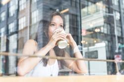 beautiful girl enjoying an hot coffee inside a shop in New york
