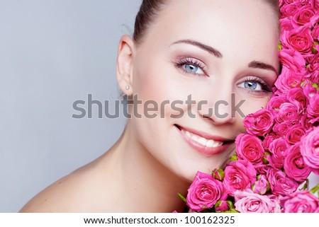 Beautiful girl face near the rose flowers