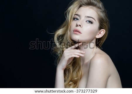 Beautiful Girl face. Perfect skin. Close-up of an attractive girl of European appearance on dark background. #373277329