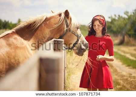 Beautiful girl feeding  her horse.