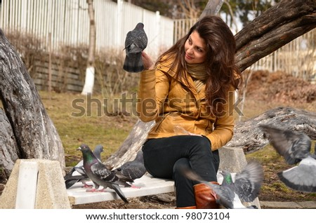 beautiful girl feeding pigeons in the park