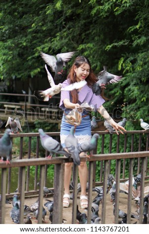 Beautiful girl feeding to pigeons, She was fear of the pigeons flying. #1143767201