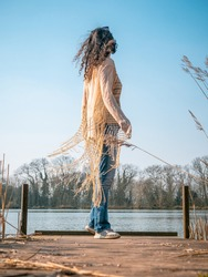 Beautiful girl gazing into the distance. Free Spirit standing on a boardwalk/fishing pier, lake and trees in background on sunny day. Wearing cream coloured Shawl.