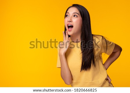 Beautiful girl gets surprised when look at copy space. Surprised happy beautiful asian woman looking copy space in exciting. use for your product, advertising. Isolated on yellow background