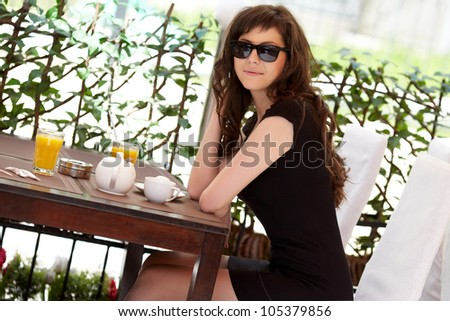 Beautiful girl having breakfast at cafe. With sun glasses.
