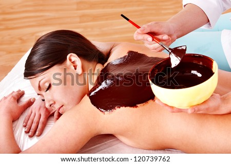 Beautiful girl having chocolate facial mask apply by beautician