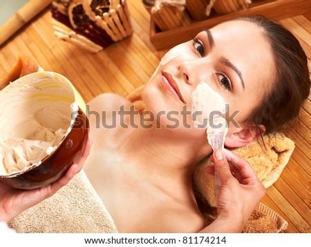 Beautiful girl having clay facial mask apply by beautician.