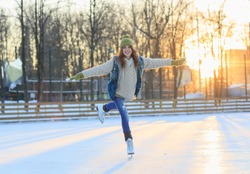 Beautiful girl having fun in winter park, balancing while skating at ice rink. Enjoying nature, winter time