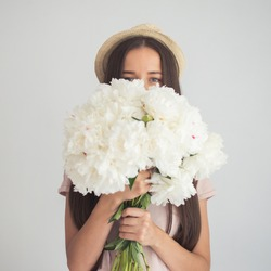 Beautiful girl hiding behind a bouquet of flowers